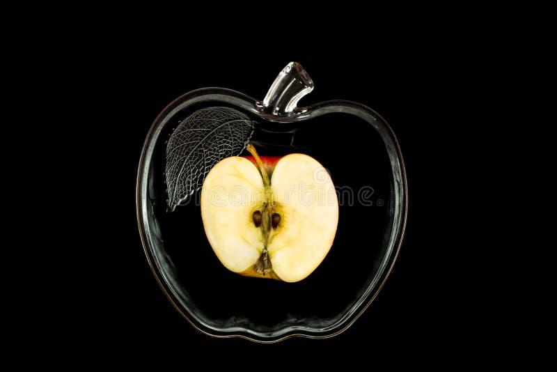 Geschnittener Apfel in einer Glasschüssel auf einem schwarzen Hintergrund stockfotografie