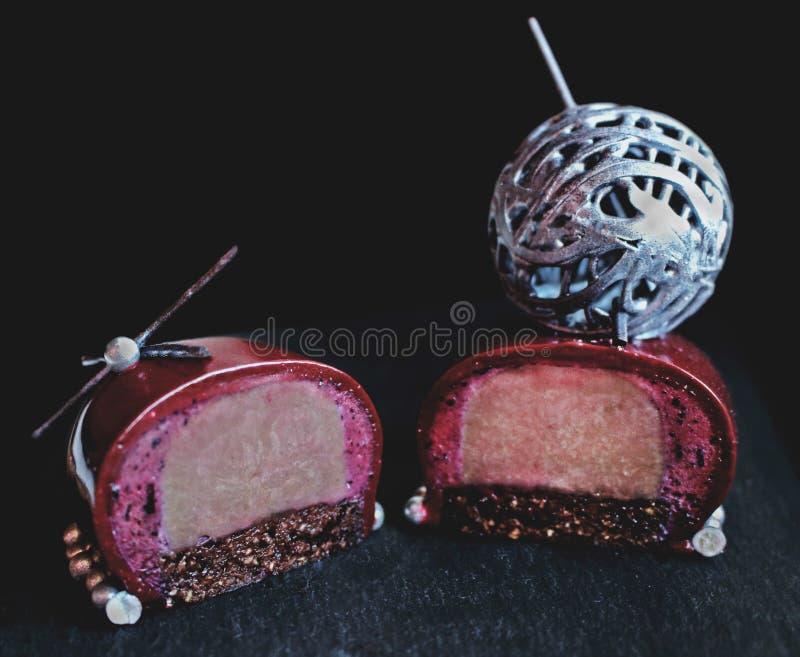 Geschnittener dunkler Schokoladenbeerennachtisch mit silberner Wollballdekoration und -schokoladenkuchen stockfotografie