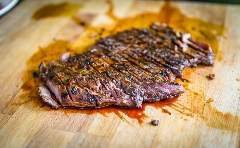 Geschnittener gegrillter saftiger marinierter Rindfleischbauchlappen auf h?lzernem Brett lizenzfreies stockbild