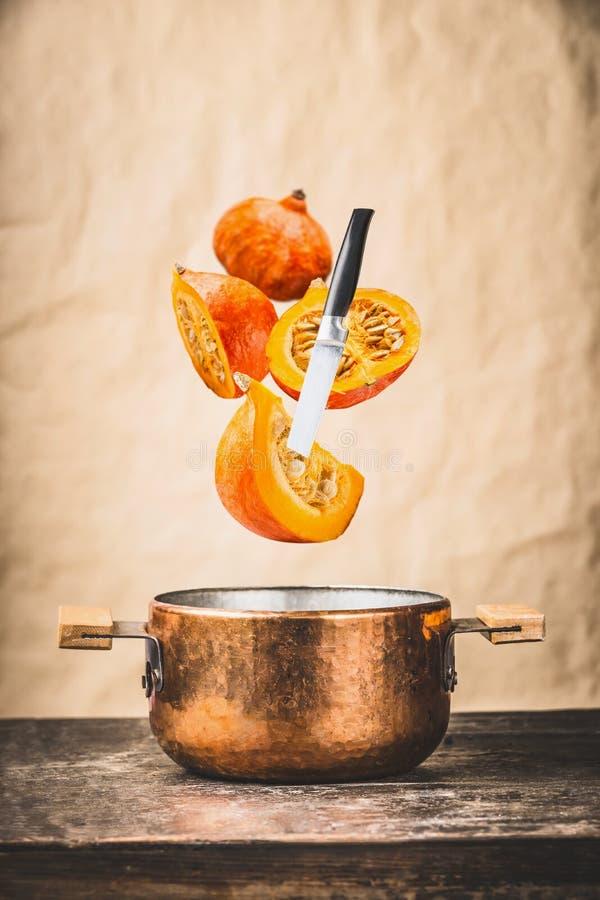 Geschnittener Kürbis mit Messer und Topf auf Holztischen am Wandhintergrund, Kürbis kochen, der Vorbereitung für Herbst Saisonrec stockfoto