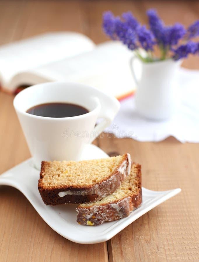 Geschnittener orange Kuchen mit Tasse Kaffee stockfotos
