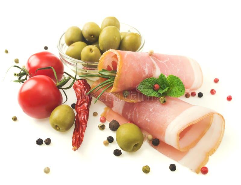 Geschnittener Prosciutto mit Rosmarin und Oliven lizenzfreie stockbilder