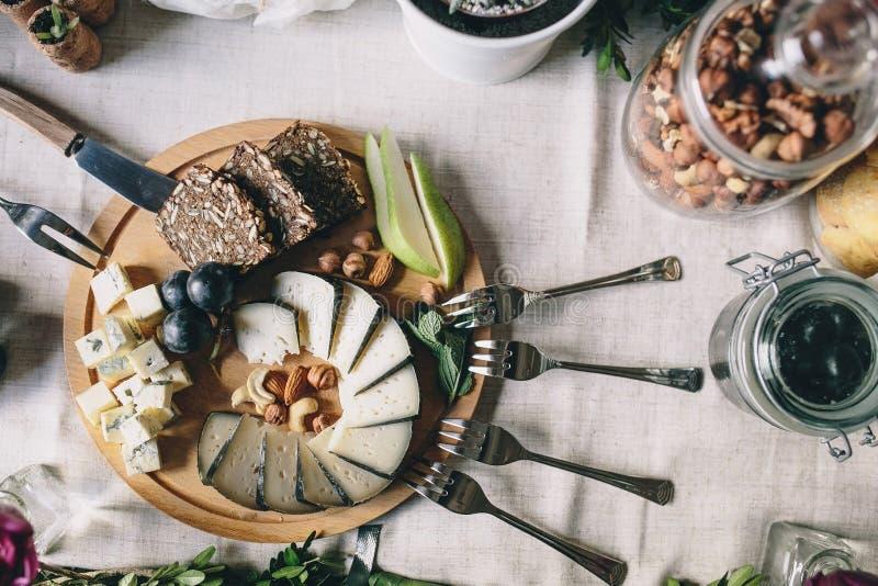 Geschnittener Ziegenkäse mit Dorblu mit Scheiben brot, Birnen, Trauben auf einer hölzernen Platte stockfotos