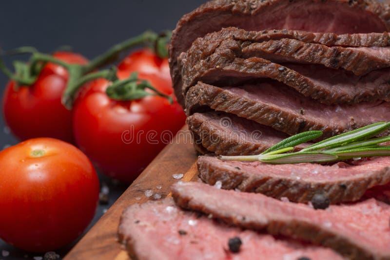 Geschnittenes bäuerisches saftiges Mais-Roastbeef geschmückt mit Tomaten, frischer Rosemary Herb und Regenbogen-Pfefferkörnern lizenzfreies stockbild