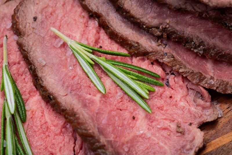 Geschnittenes bäuerisches saftiges Mais-Roastbeef schmückte mit Rosemary Fresh Herb auf Naturholzschneidebrett stockbilder