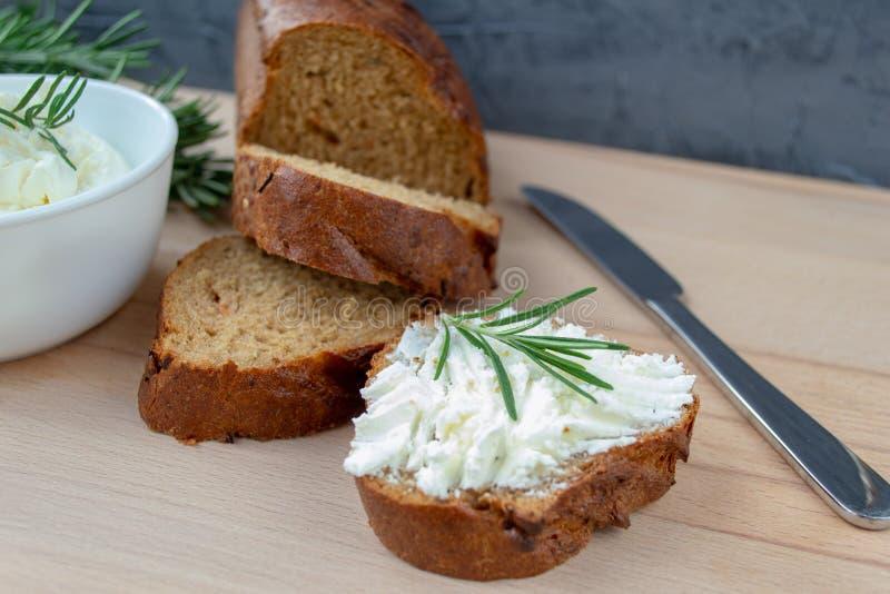 Geschnittenes Brot mit hellem K?se auf einem h?lzernen Brett lizenzfreie stockfotografie