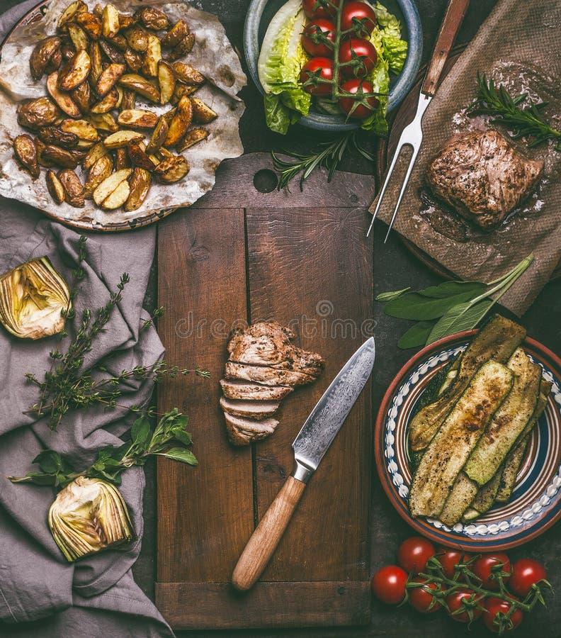 Geschnittenes gebratenes Schweinefleisch und Küchenmesser auf Schneidebrett mit Ofenkartoffeln, Zucchini und Salat stockfotografie