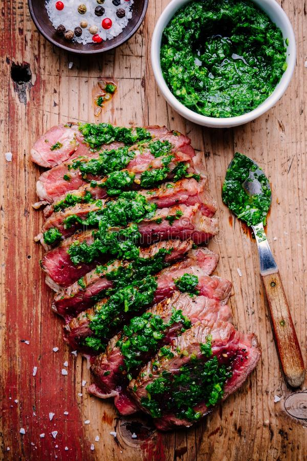 Geschnittenes gegrilltes Grillrindfleischsteak mit grüner chimichurri Soße stockfoto