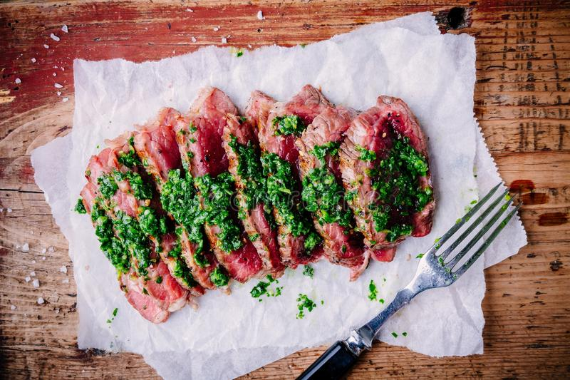 Geschnittenes gegrilltes Grillrindfleischsteak mit grüner chimichurri Soße lizenzfreie stockfotografie