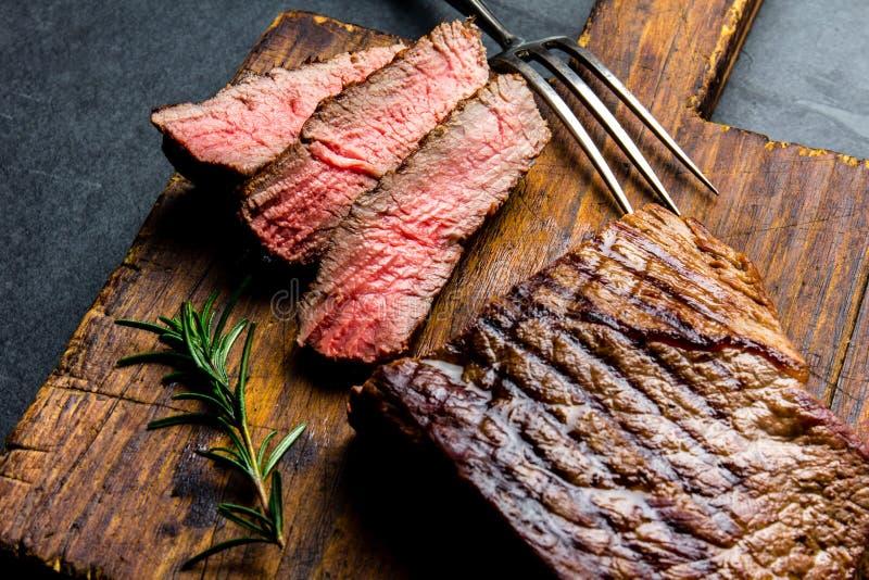 Geschnittenes gegrilltes halb gares Rindfleischsteak diente auf hölzernes Brett Grill, bbq-FleischRindsfilet Draufsicht, Schiefer stockfotos