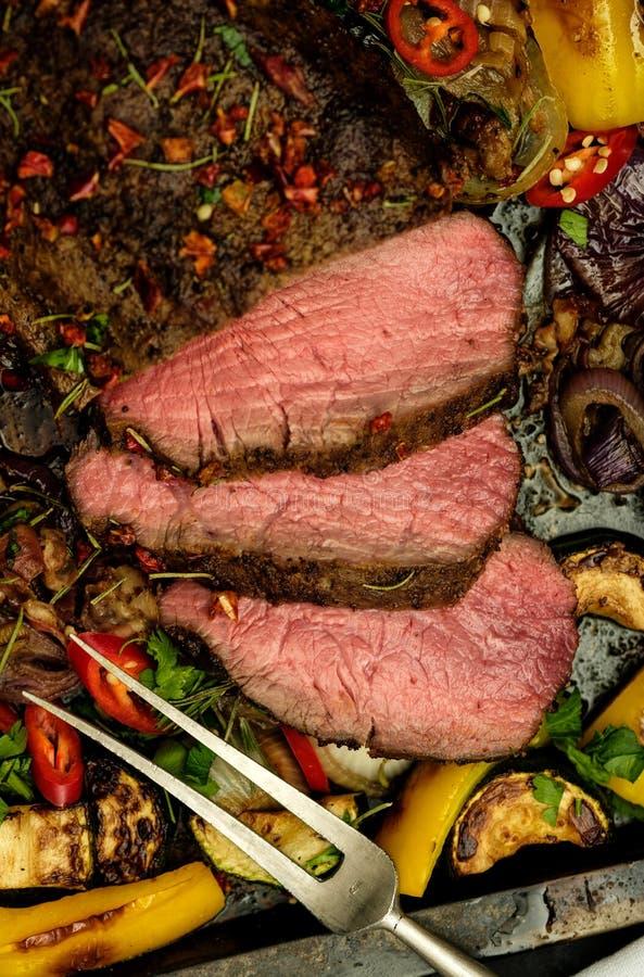 Geschnittenes gegrilltes Rindfleischrumpsteak auf Backblech mit Gemüse lizenzfreie stockfotos