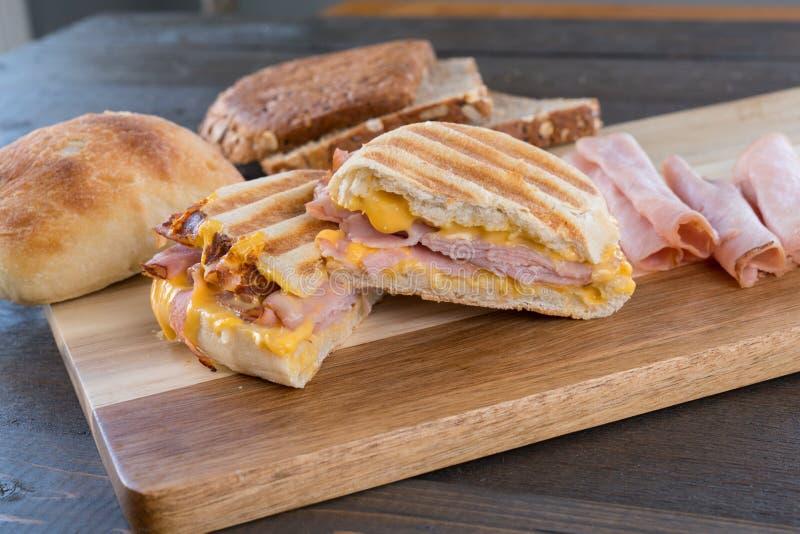 Geschnittenes gegrilltes Schinken und Käse Panini-Sandwich lizenzfreie stockbilder