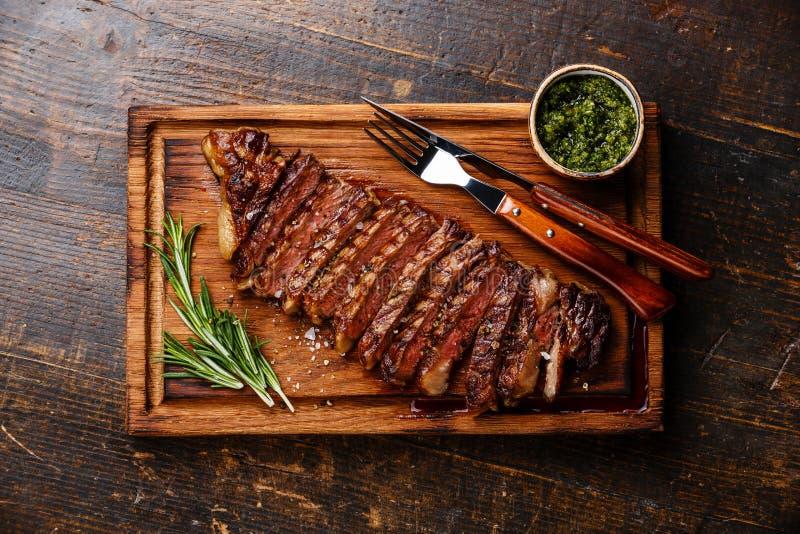 Geschnittenes gegrilltes Striploin-Steak mit chimichurri Soße lizenzfreies stockbild