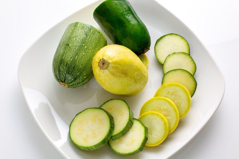 Geschnittenes gelbes und grünes Zucchini ` s auf einer weißen Platte, die auf einem Küchentisch wartet verbraucht zu werden sitzt stockbilder
