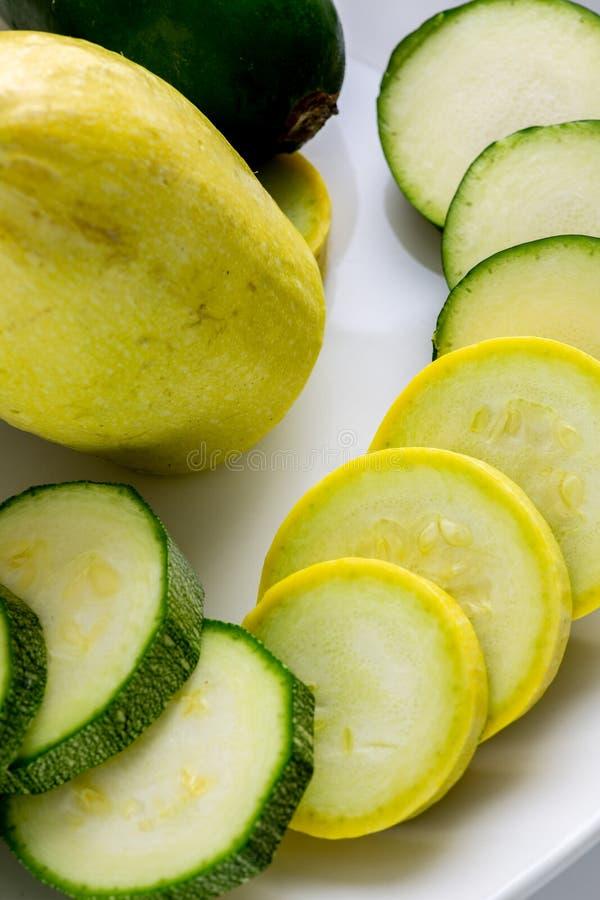 Geschnittenes gelbes und grünes Zucchini ` s auf einer weißen Platte, die auf einem Küchentisch wartet verbraucht zu werden sitzt stockfoto