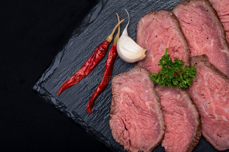 Geschnittenes Gras Fed Corn Roast Beef schmückte mit Knoblauch, frischer gelockter Petersilie und getrocknetem rotem Chile De Arb stockbild