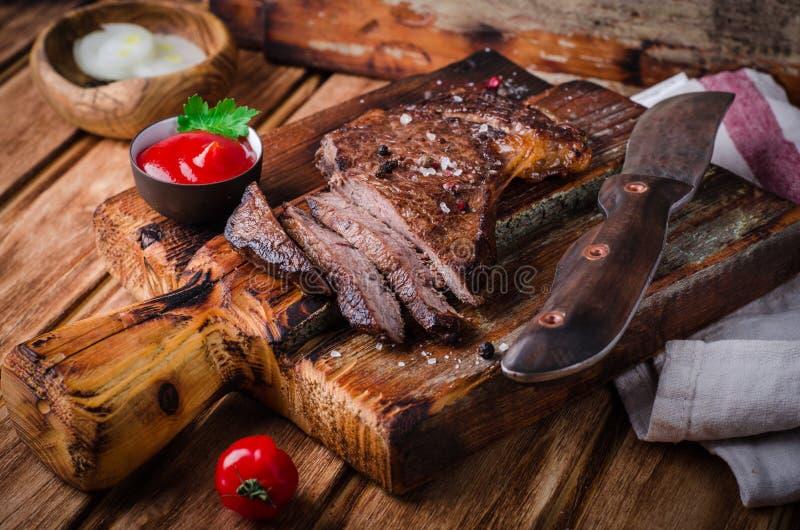 Geschnittenes halb gares gegrilltes Rindfleischsteak mit Gewürzen und Ketschup auf Schneidebrett auf hölzernem Hintergrund lizenzfreie stockfotografie