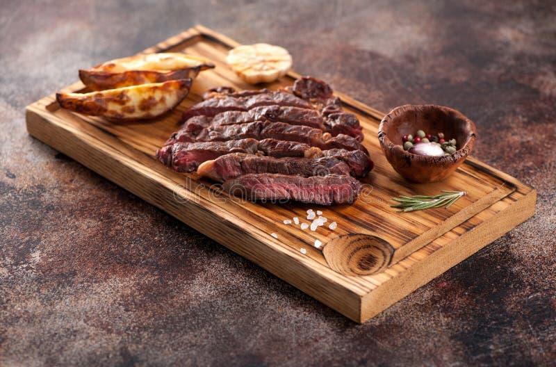 Geschnittenes halb gares gegrilltes Rindfleischsteak ribeye mit gebratenen Kartoffeln stockbilder