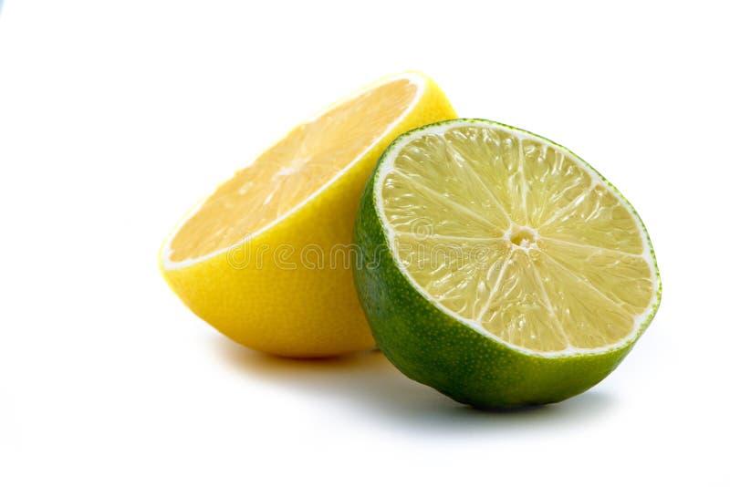 Geschnittenes Limet und Zitrone auf weißem Schreibtisch stockbilder