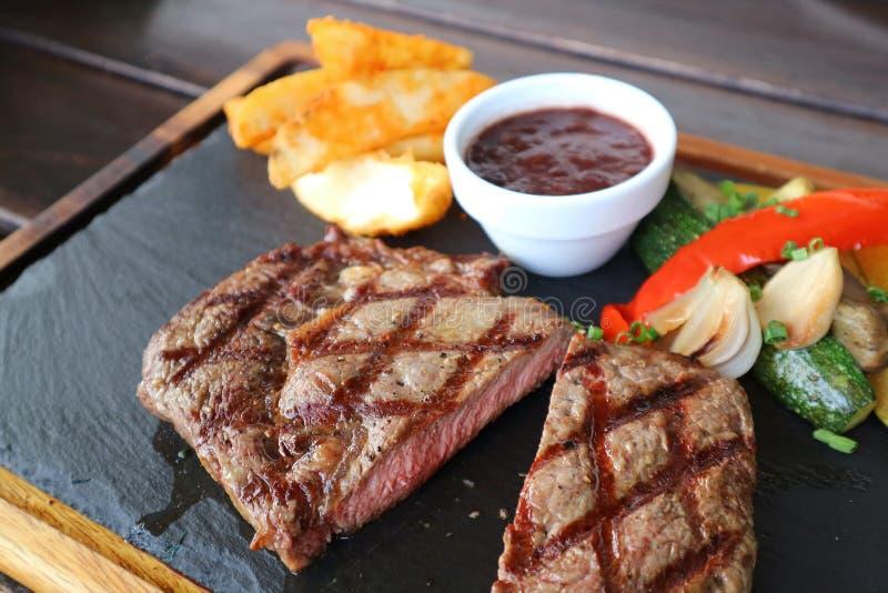 Geschnittenes mittleres gegrilltes ribeye Steak mit Rotweinsoße und Gemüse auf heißer Steinplatte sautieren stockfoto