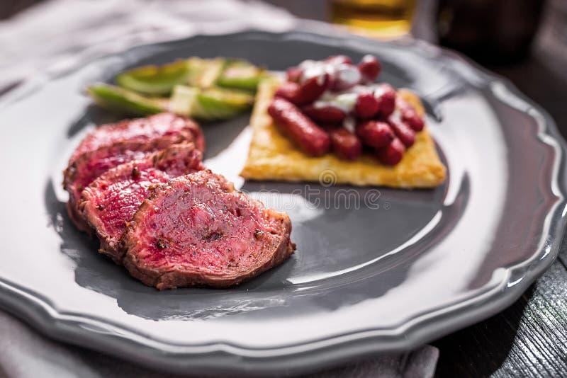 Geschnittenes Rindfleischsteak mit gegrilltem Gemüse auf einer Platte lizenzfreies stockbild