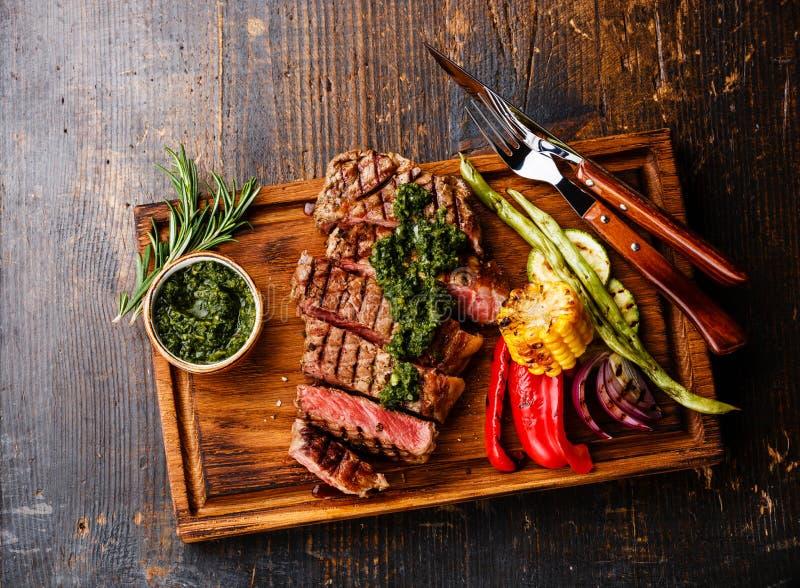 Geschnittenes Striploin-Steak mit chimichurri Soße und Gemüse lizenzfreies stockfoto