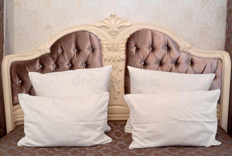 Geschnitzte Kopfende eines Doppelbetts mit Kissen lizenzfreie stockfotos