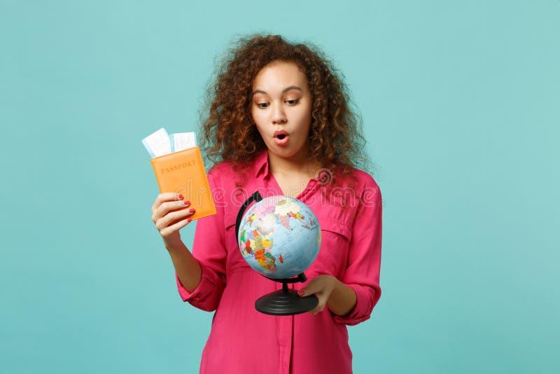 Geschokt Afrikaans meisje die in die vrijetijdskleding de bol van de Aardewereld, het kaartje van de paspoort instapkaart houden, royalty-vrije stock afbeeldingen