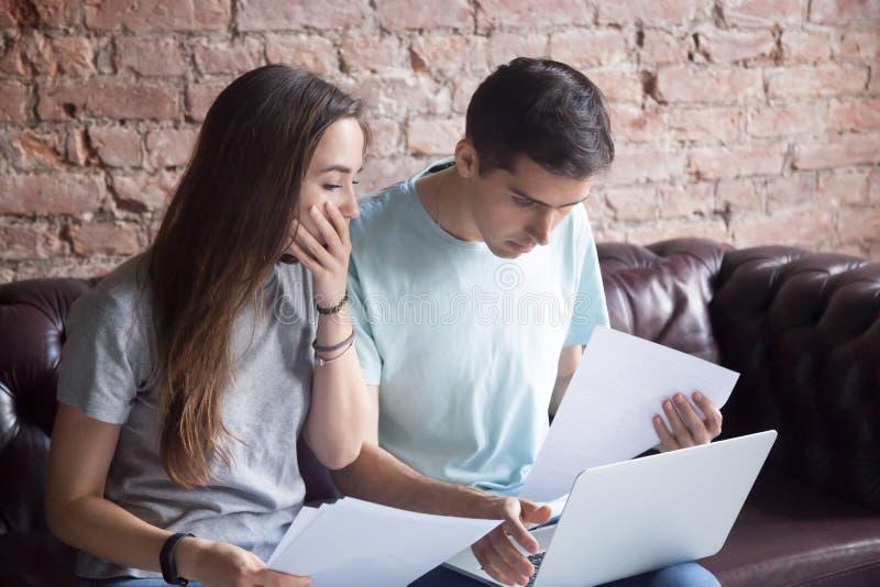 Geschokt jong paar die documenten en laptop bekijken stock foto's