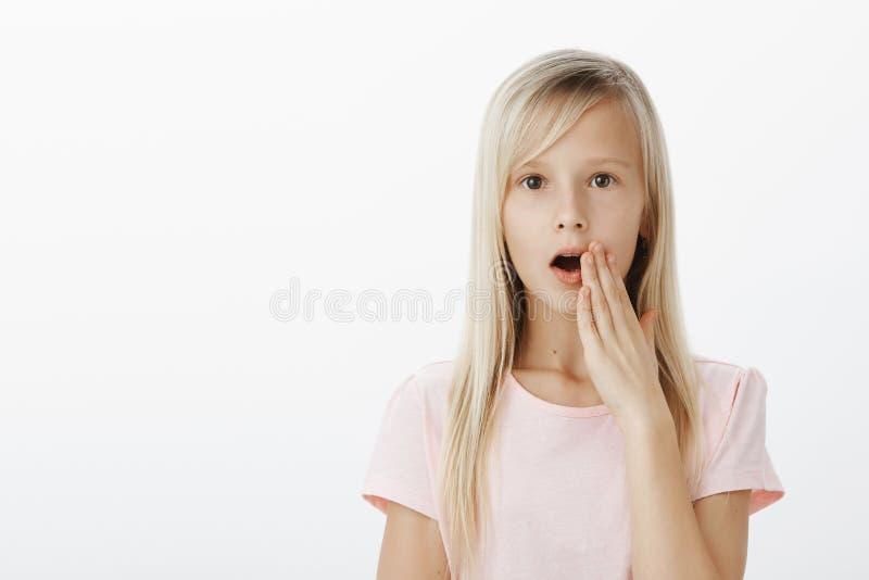 Geschokt leuk Europees meisje met blond haar, uitspreidende geruchten of roddels in klaslokaal, die palm houden dichtbij mond ter royalty-vrije stock fotografie