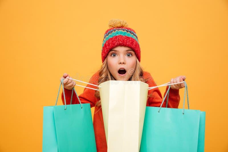 Geschokt meisje in sweater en hoed holdings en het openen pakketten royalty-vrije stock afbeeldingen