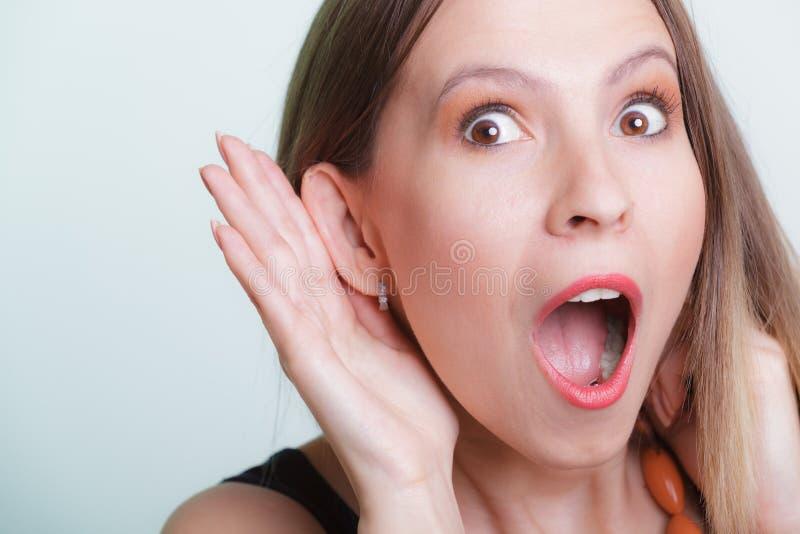 Geschokt roddelmeisje die met hand aan oor afluisteren stock afbeelding