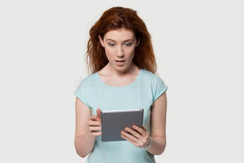 Geschokt roodharig verrast meisje het krijgen van bericht op tablet stock afbeeldingen