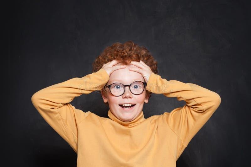 Geschokt schadelijk kind met haar hoofd in haar hand op bordachtergrond stock foto's