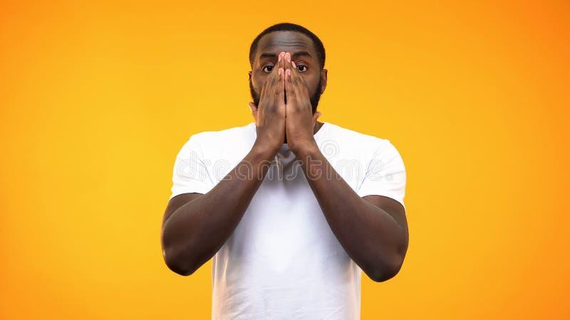 Geschokt zwart mannetje die gezicht door handen, probleemverbazing, verbazing behandelen stock foto