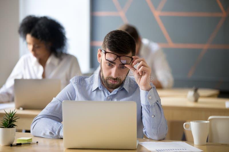Geschokte die zakenman door nieuws wordt overweldigd die laptop in coworki bekijken royalty-vrije stock foto