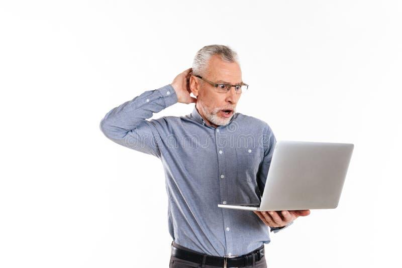 Geschokte geïsoleerde mens in oogglazen die laptop computer met behulp van royalty-vrije stock foto's
