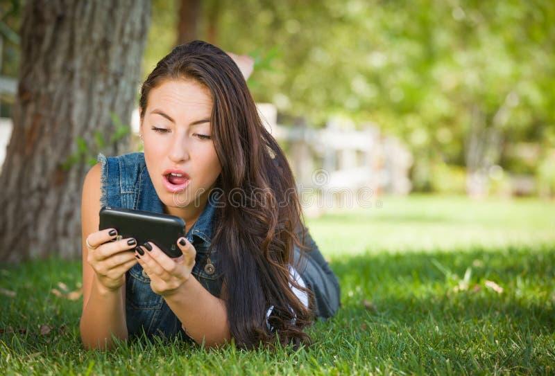 Geschokte Gemengde Race Jonge Vrouwelijke Texting op Haar Celtelefoon buiten royalty-vrije stock fotografie