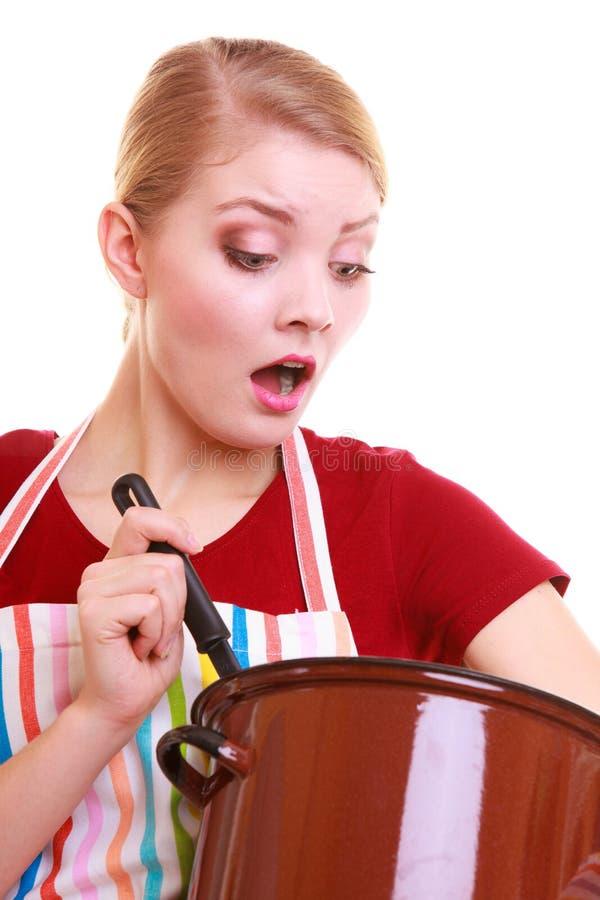Geschokte huisvrouw of chef-kok in keukenschort met pot van pollepel stock foto