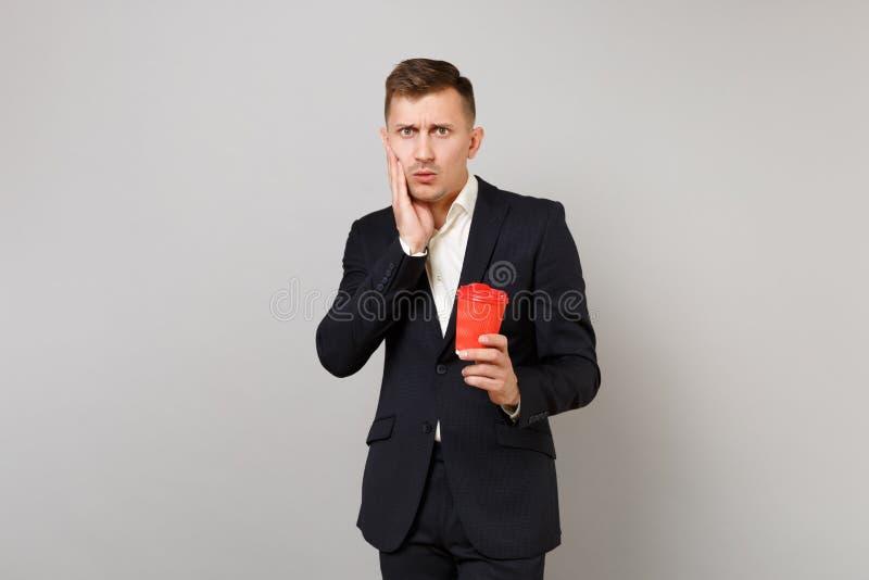 Geschokte jonge bedrijfsmens die in klassiek zwart kostuum hand op het document van de wangholding kop met koffie of geïsoleerde  stock foto's