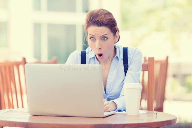Geschokte jonge bedrijfsvrouw die laptop met behulp van die het computerscherm bekijken stock fotografie