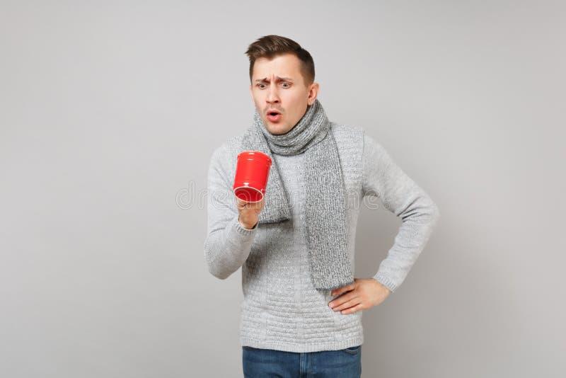 Geschokte jonge mens die in grijze sweater, sjaal rode kop van koffie of thee op grijze muurachtergrond onderzoeken Gezond royalty-vrije stock afbeelding