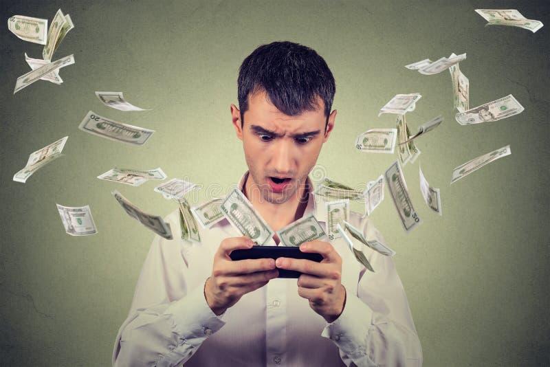 Geschokte jonge mens die smartphone met de bankbiljetten gebruiken die van dollarrekeningen wegvliegen stock foto's