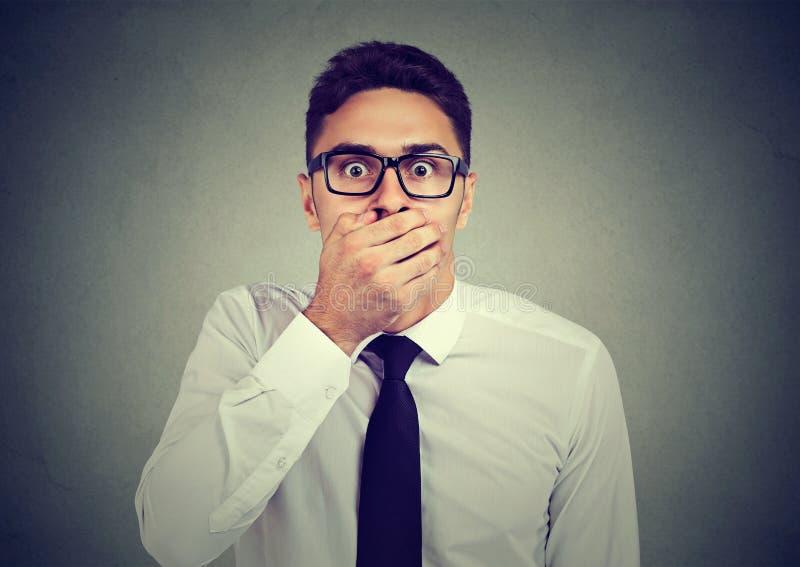 Geschokte jonge mens die zijn mond behandelen met hand royalty-vrije stock afbeelding
