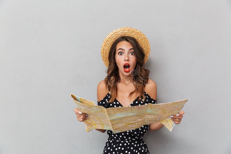 Geschokte jonge vrouw die de kaart van de hoedenholding over grijze muur dragen stock foto's