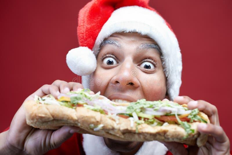 Geschokte Kerstman die Heerlijke Hamburger eten stock afbeeldingen