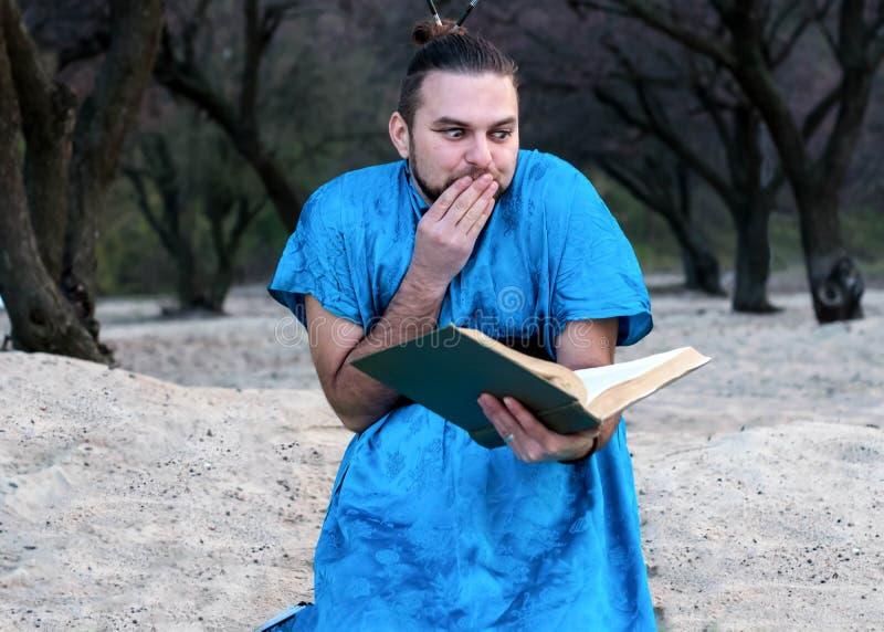 Geschokte knappe gebaarde mens in blauw van de kimonozitting en lezing boek royalty-vrije stock afbeeldingen