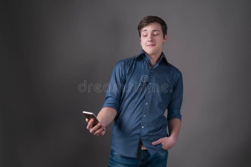Geschokte knappe jonge mens in blauw overhemd die en smartphone glimlachen bekijken royalty-vrije stock fotografie