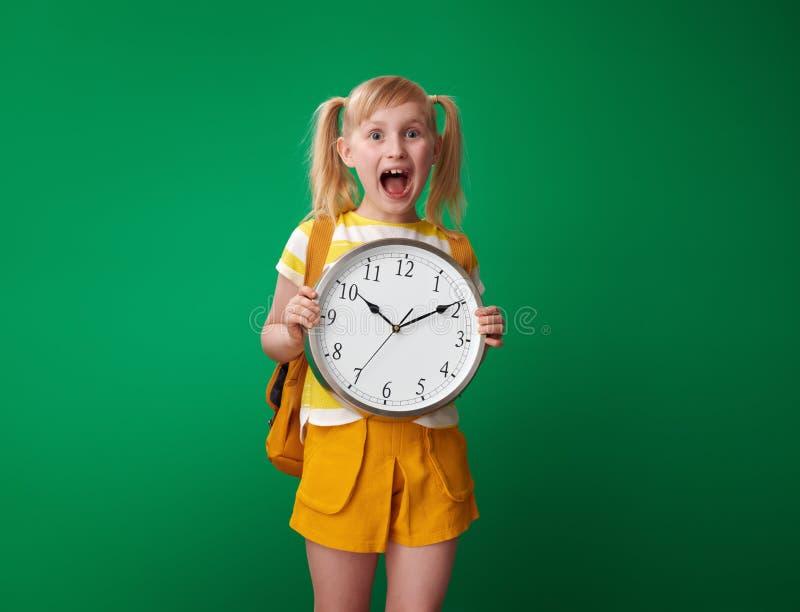 Geschokte leerling die die klok tonen op groene achtergrond wordt geïsoleerd stock afbeelding