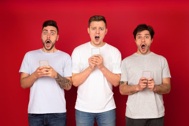 Geschokte mannelijke vrienden met telefoons, die Internet surfen stock afbeelding